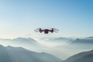 Drone in sky above mountains sunny day