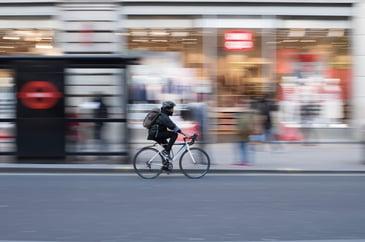 Man on pedal bike outside bus stop in London